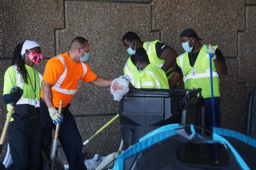 Houston solid waste department employees assist in a homeless encampment cleanup.