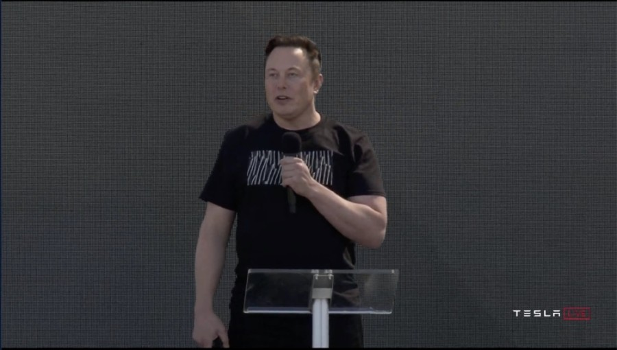 A screen shot of Elon Musk speaking into a microphone