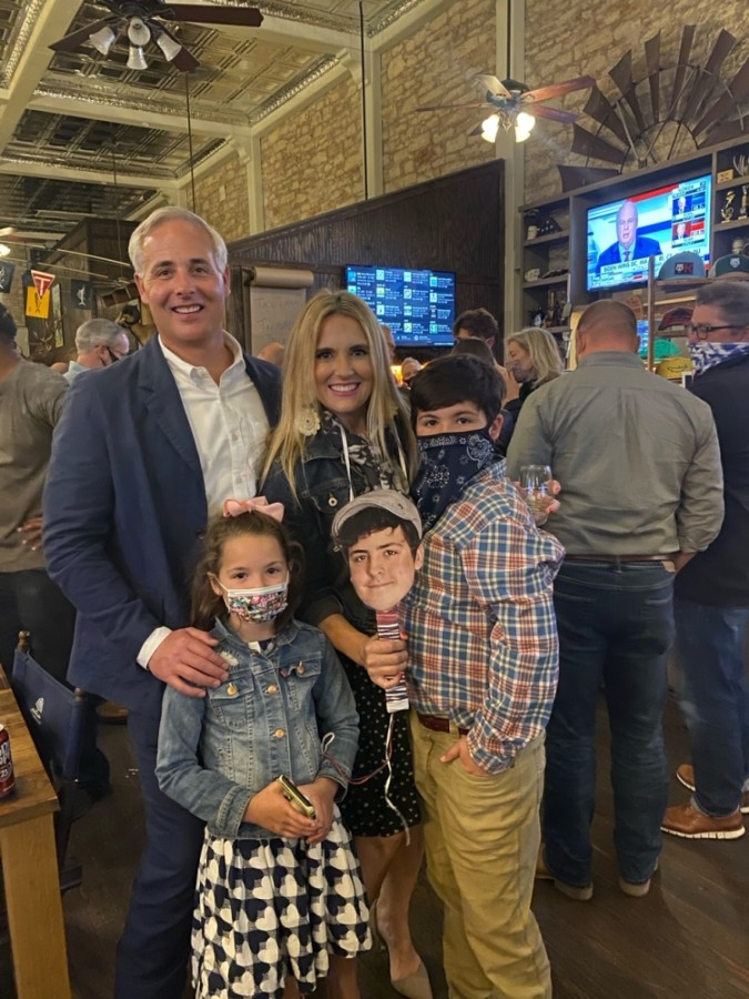 Josh Schroeder is seen with his family Nov. 3 at Mesquite Creek Outfitters, where they watched the election results come in. Schroeder's oldest son was in quarantine, so the family brought a picture of him so he could be included in photos from the occasion. (Courtesy Josh Schroeder)