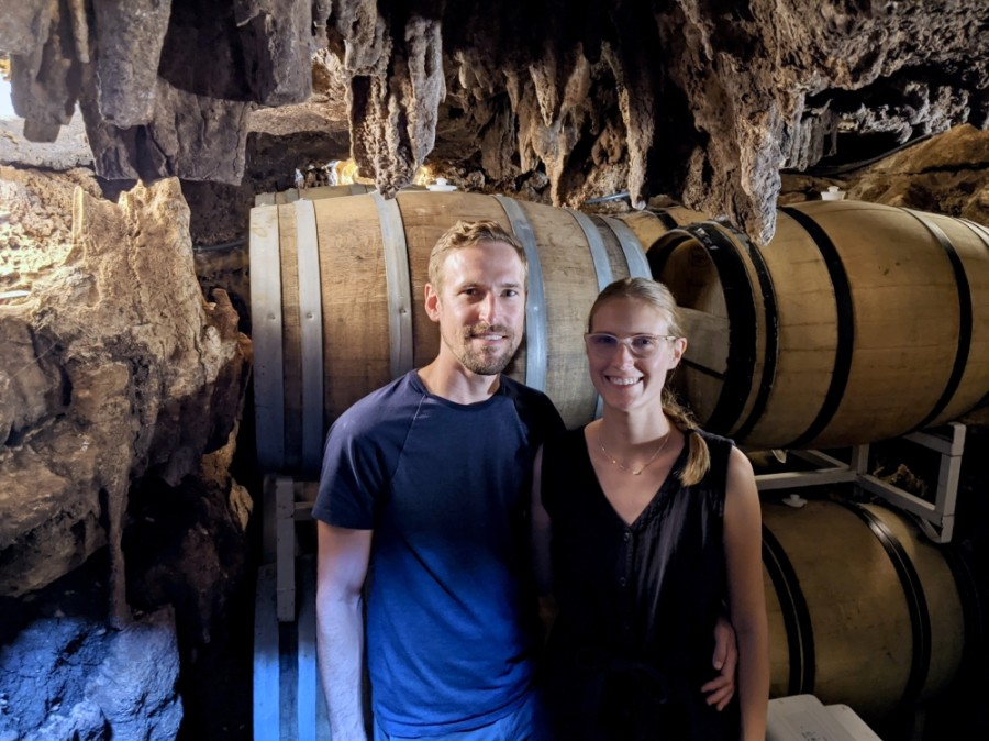 Founders Davy and Alex Pasternak stand with several barrels of beer fermenting in a cave at Roughhouse Brewing. (Warren Brown/Community Impact Newspaper)