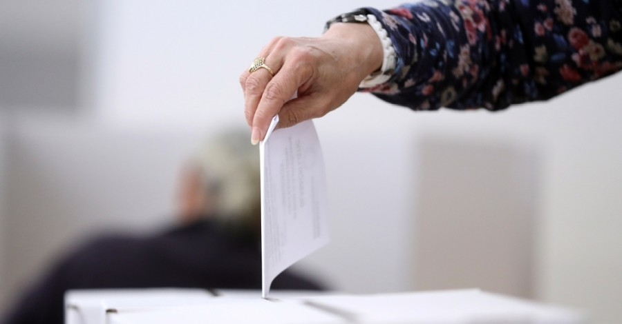 Photo of a hand dropping a ballot in a box