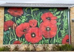 "Wolf Ranch Town Center unveiled its new exterior mural on Dec. 2. The mural titled ""Dreaming of Papaver Rhoeas"" was designed by local artist Angela Effenberger. (Courtesy Wolf Ranch Town Center)"