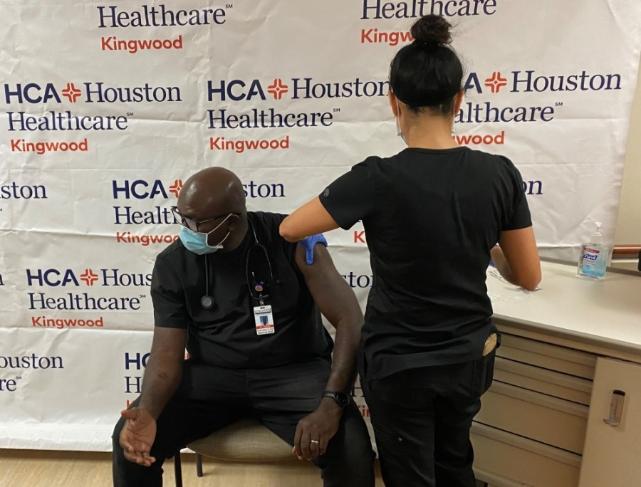 HCA Houston Healthcare Kingwood nurse Erica Reyes administers the first dose of the Pfizer COVID-19 vaccine to Dr. Akinyinka Ajelabi, a pulmonologist, on Friday, Dec. 18. (Courtesy HCA Houston Healthcare Kingwood)