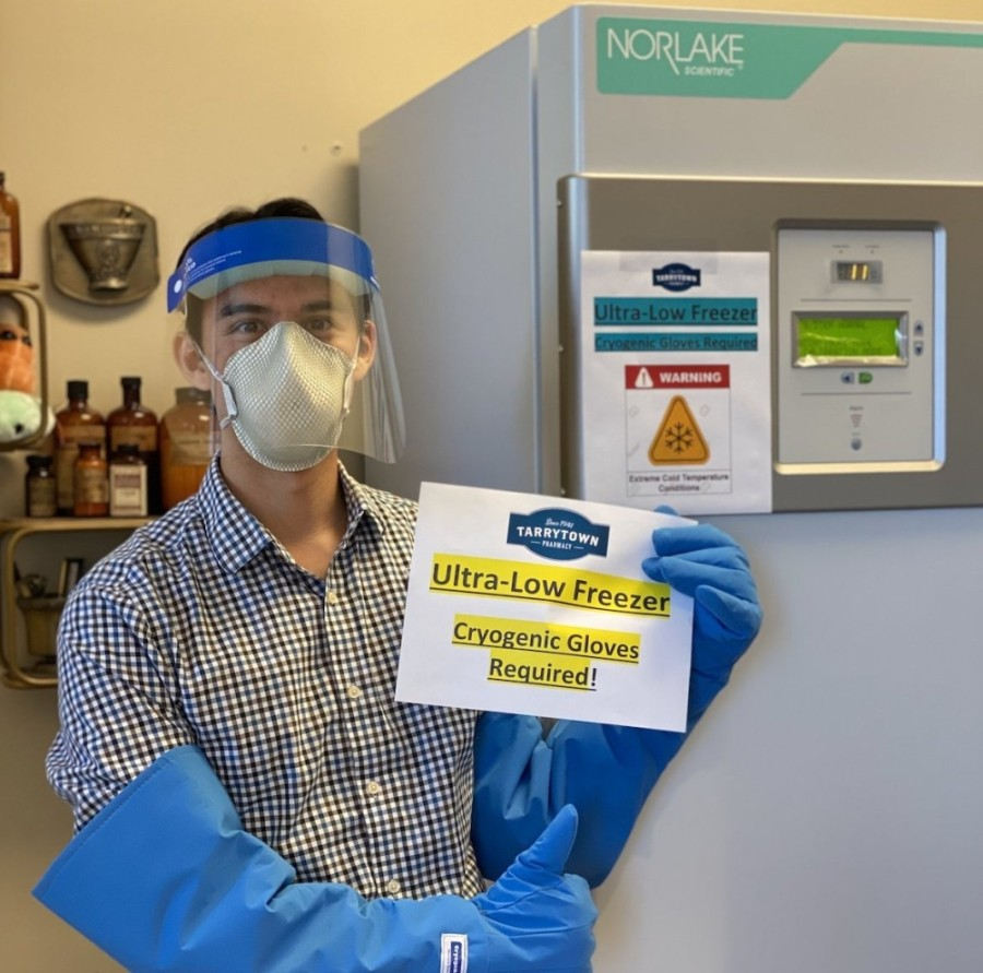Photo: pharmacist in PPE standing in front of ultra-low freezer
