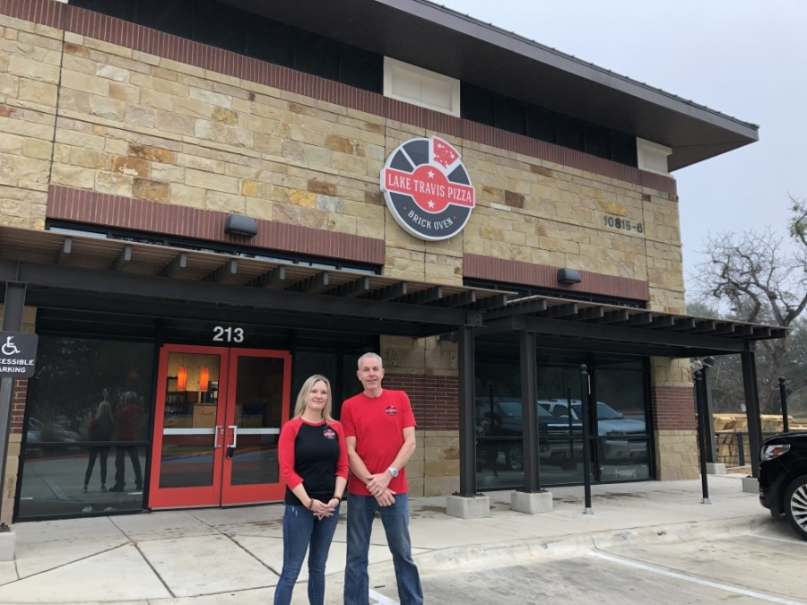 Leah and Mark Mirra stand in front of their upcoming location of Lake Travis Pizza in the River Place neighborhood. (Amy Rae Dadamo/Community Impact Newspaper)