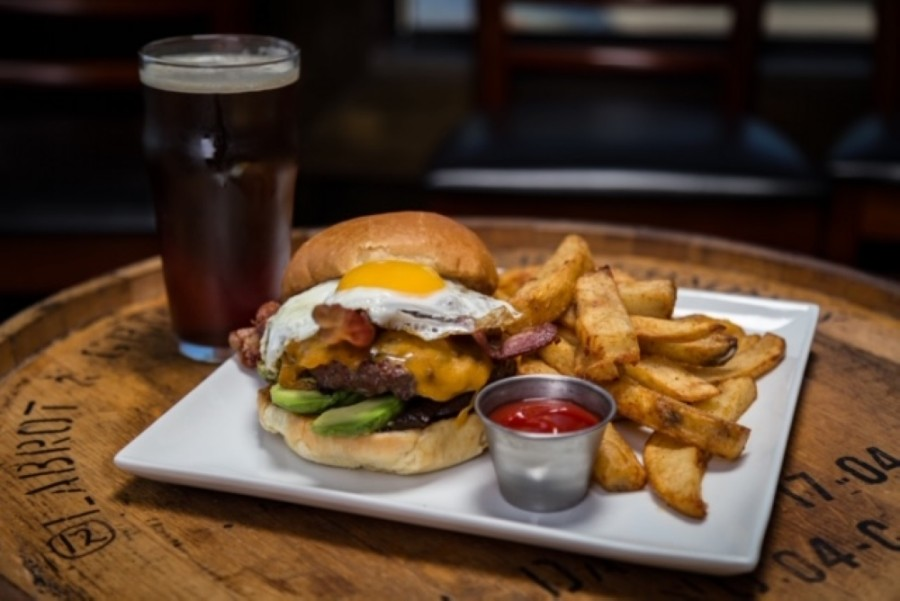The fried egg burger ($13) is an 8 oz. beef burger on a brioche bun topped with a fried egg, bacon, avocado, cheddar cheese and caramelized onions, served with fries.