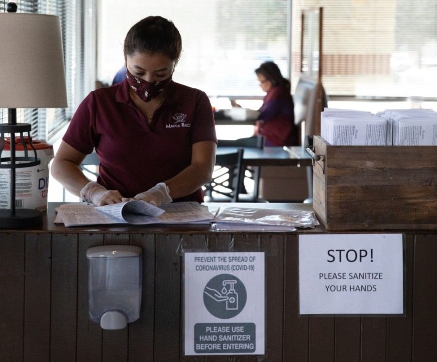 A hostess at Maple Bacon folds single-use menus ahead of the arrival of customers. (Liesbeth Powers/Community Impact Newspaper)