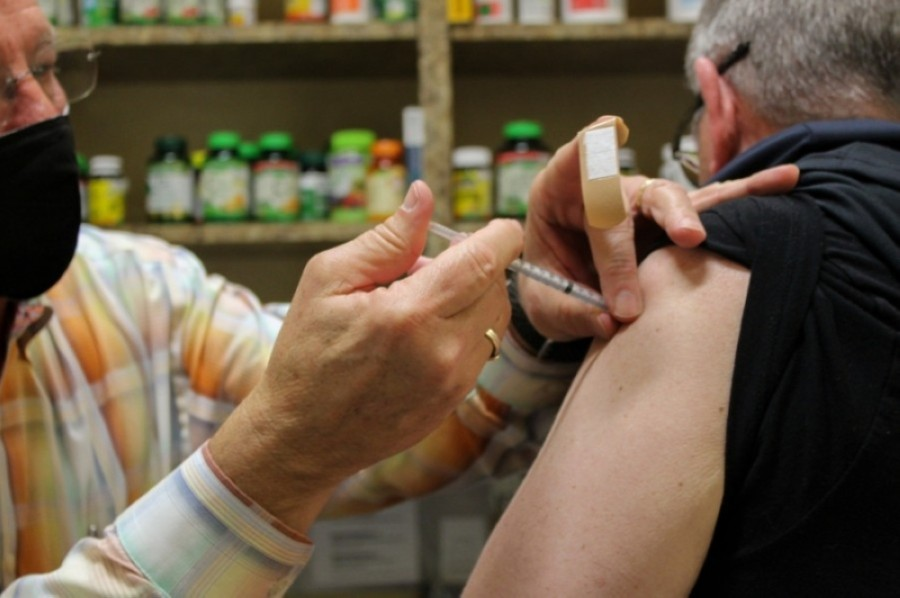 Scott Palmer administers a COVID-19 vaccine shot to a Roanoke police officer. (Sandra Sadek/Community Impact Newspaper)