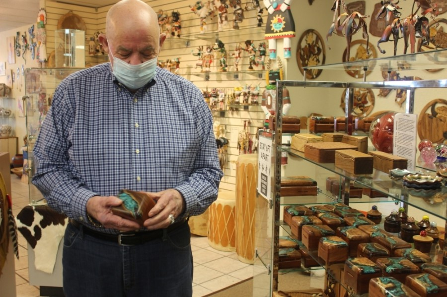 Turquoise Trading Post owner Jim Williamson looks at a handmade wooden box set with turquoise. (Olivia Aldridge/Community Impact Newspaper)