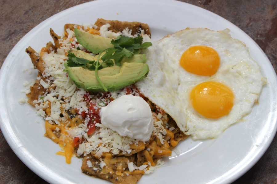 Rafaela's Chilaquiles ($10.99) include custom-prepared eggs accompanied by a house tomatillo salsa verde, fried tortilla chips, cheddar and cotija cheeses, pico de gallo, avocado, sour cream and cilantro. Meat can also be added. (Ben Thompson/Community Impact Newspaper)
