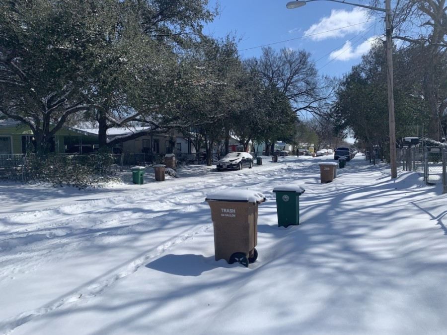 Photo of a street and trash bins covered in snow