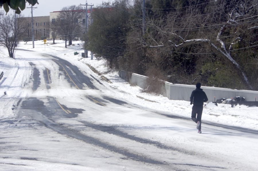 A jogger runs up a nearly deserted Manor Road in Austin on Feb. 16, two days after a winter storm dropped six inches of snow in the area. (Jack Flagler/Community Impact Newspaper)