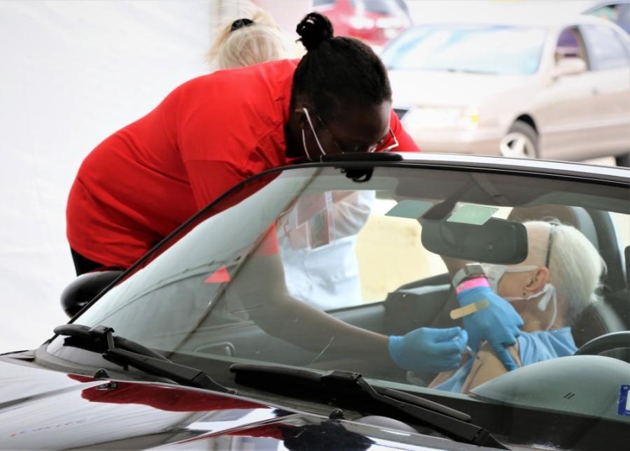 nurse administering vaccine in car