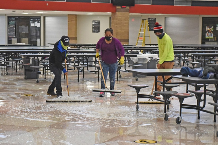 Restoration crews work to clean up water from the floors following freezing temperatures this week that caused pipe damage to campuses. (Courtesy Cy-Fair ISD)