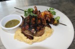 The bacon-wrapped center-cut ribeye, a special item not on the menu, ($28) is served on a bed of artismal grits and Brussels sprouts with fresh shrimp kabobs. (Eva Vigh/Community Impact Newspaper)