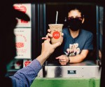Photo of a Joe's coffee barista handing off a drive-thru coffee