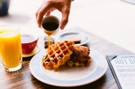 Chicken and waffles are served with syrup. (Courtesy Layered)