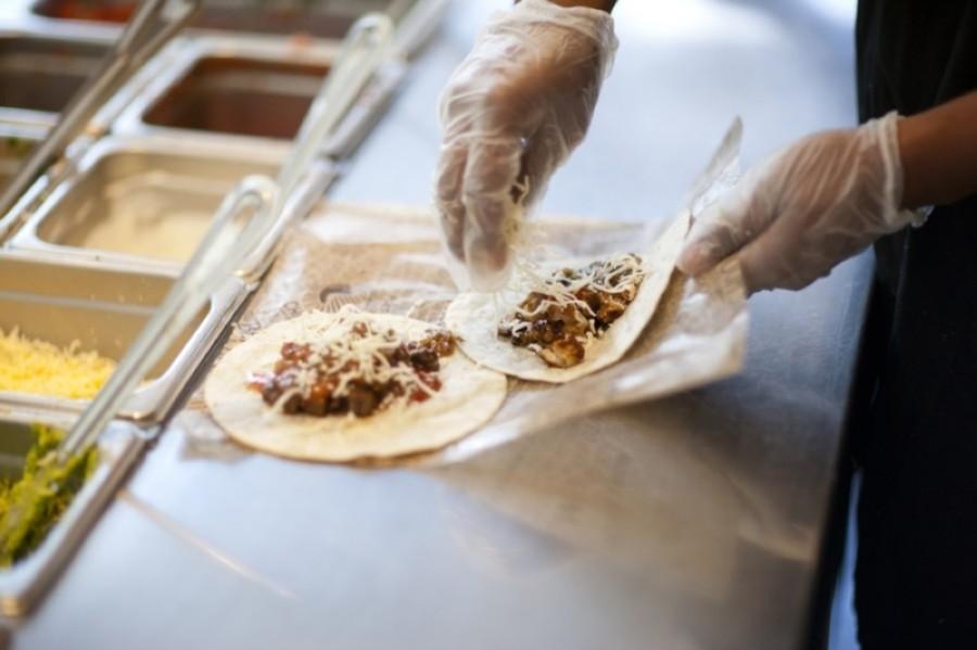 Chipotle employee making two burritos