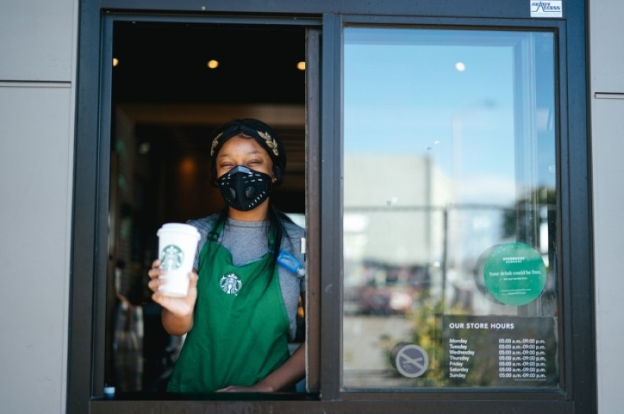 Starbucks employee standing at a drive-thru window, holding a drink