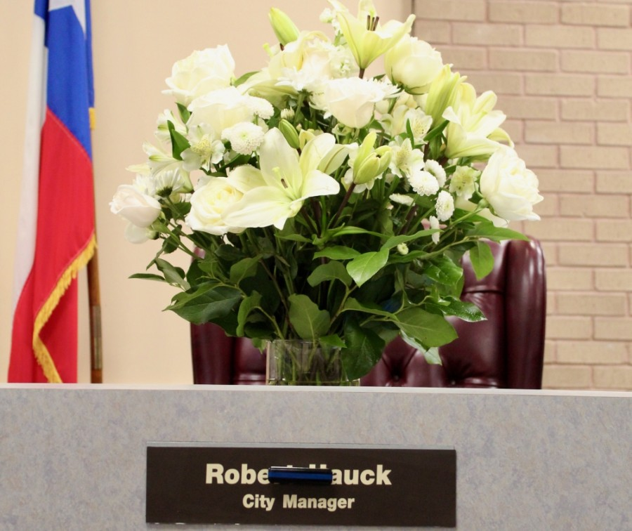 At a March 15 City Council meeting, a bouquet of flowers sat in the place of City Manger Rob Hauck. (Anna Lotz/Community Impact Newspaper)