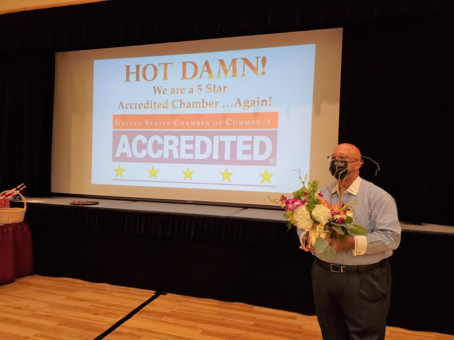 Phil Cunningham, chairman of the Grapevine Chamber of Commerce Board of Directors, presents flowers as the five-star accreditation is announced. (Courtesy Grapevine Chamber of Commerce)