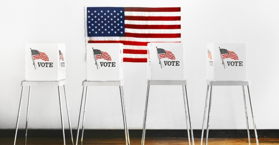 """Photo of a series of """"vote"""" signs with an American flag"""