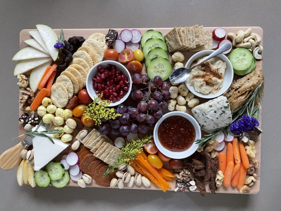 A charcuterie board featuring fruits, vegetables, crackers and cheese
