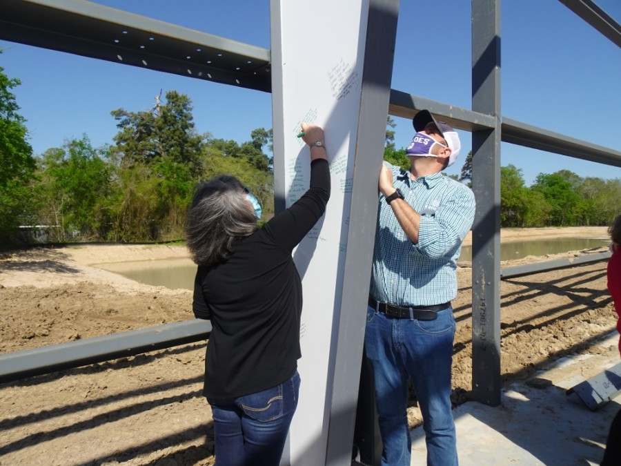 Cypress Assistance Ministries employees, board members and community partners were invited to leave messages and signatures on a beam in the organization's new building March 26. (Danica Lloyd/Community Impact Newspaper)