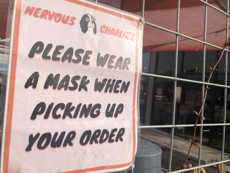 A sign at Nervous Charlie's bagel shop in north Central Austin reminds customers to wear a mask. (Jack Flagler/Community Impact Newspaper)