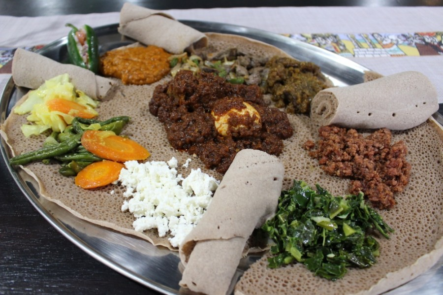 Ethiopian food is eaten communally, with groups gathering around a plate of food. (Photos by Olivia Lueckemeyer/Community Impact Newspaper)