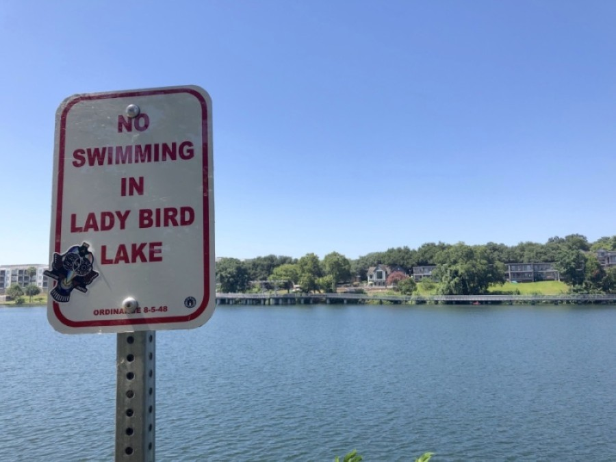 A sign along the Ann and Roy Butler Hike and Bike trail reminds residents not to swim in Lady Bird Lake. (Jack Flagler/Community Impact Newspaper)