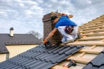 A man installing new roof tiles