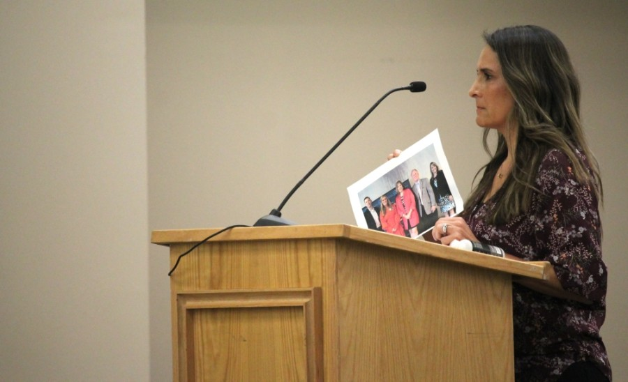 Priscilla Lashley, a KISD parent, hold a photo of Superintendent Jenny McGown maskless at a recent North Houston Association event. (Andy Li/Community Impact Newspaper)