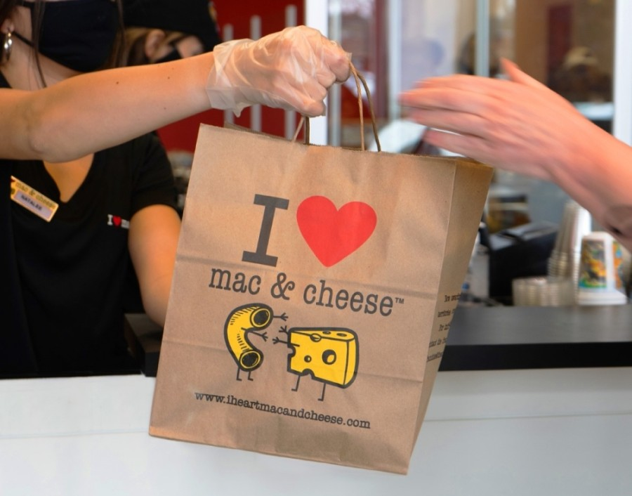 A restaurant worker handing an I Heart Mac & Cheese bag to a customer