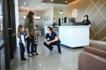 A doctor greeting a mom and two kids inside an urgent care waiting room