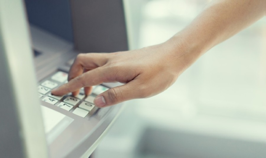 A hand typing on an ATM keypad