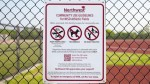 A community use guidelines sign on a fence near an athletic track