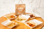 Take-out containers of food on a table surrounding a Hoots Wings bag