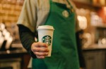 A Starbucks worker holding a to-go cup