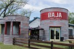 "The exterior of a corrugated metal building blazoned with the word ""BAJA."""