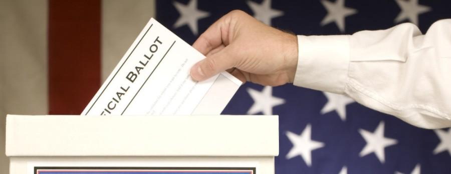 A hand depositing a ballot into a ballot box.