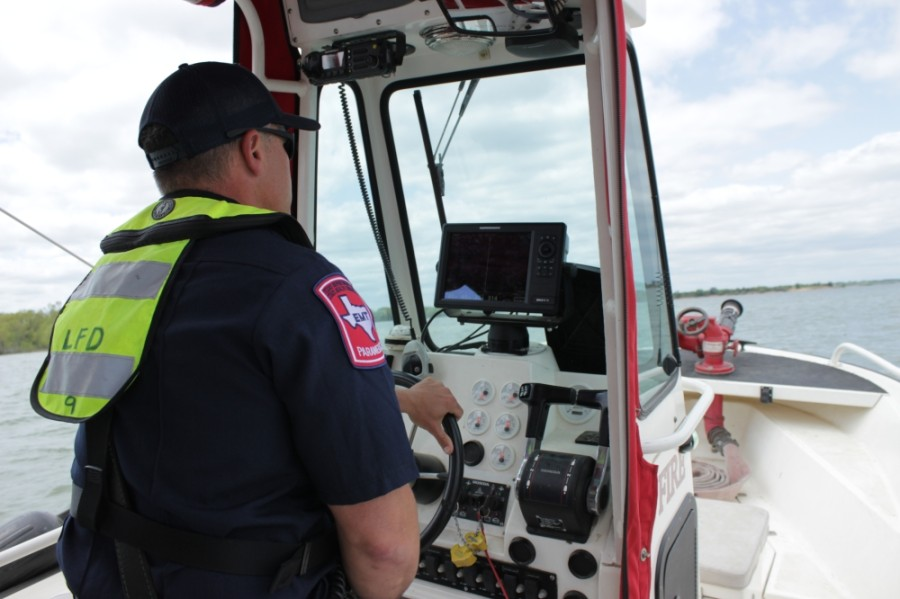 Lewisville firefighter Mike Farley operates a boat.