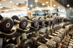 Rows of dumbbells on racks by mirrors