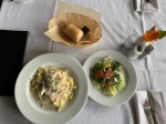Fettuccine with chicken Alfredo, a house salad and complimentary bread are some of the food items offered at Milano Ristorante. (Megan Cardona/Community Impact Newspaper)