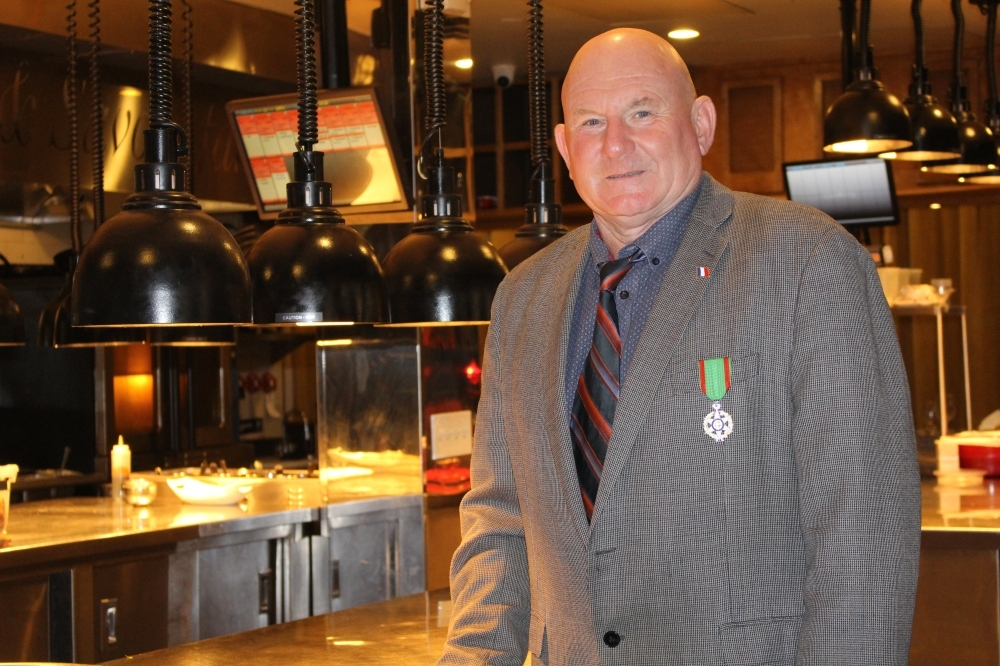 Jacques Fox, chef and owner of Artisans Restaurant in Midtown, stands in front of his French restaurant's kitchen, wearing his medallion bestowed on him on July 1. (Andy Yanez/Community Impact Newspaper).