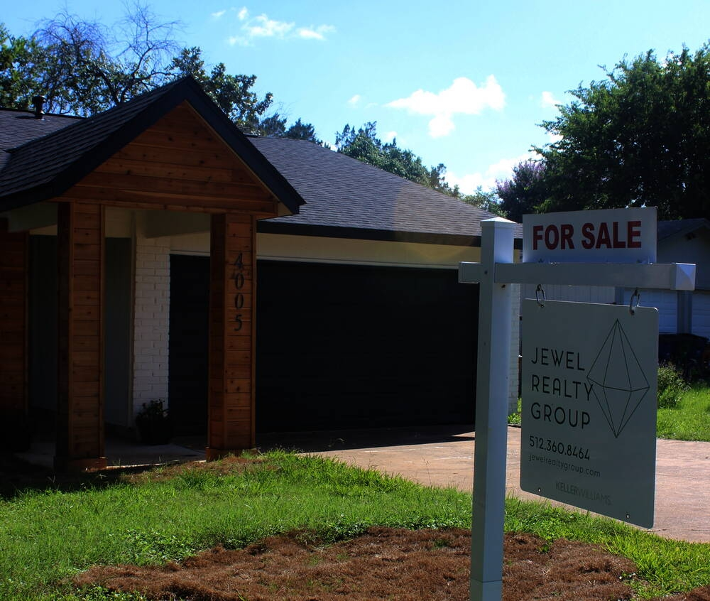 """Photo of a house with a """"for sale"""" sign in the front yard"""