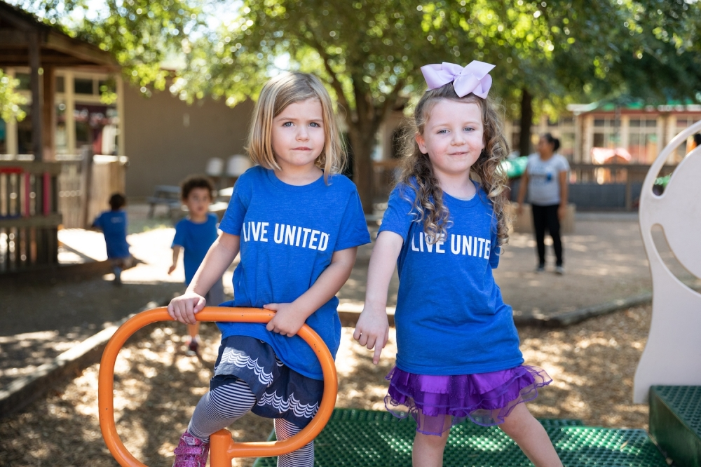 """Photo of two girls on a playground with """"Live United"""" shirts"""