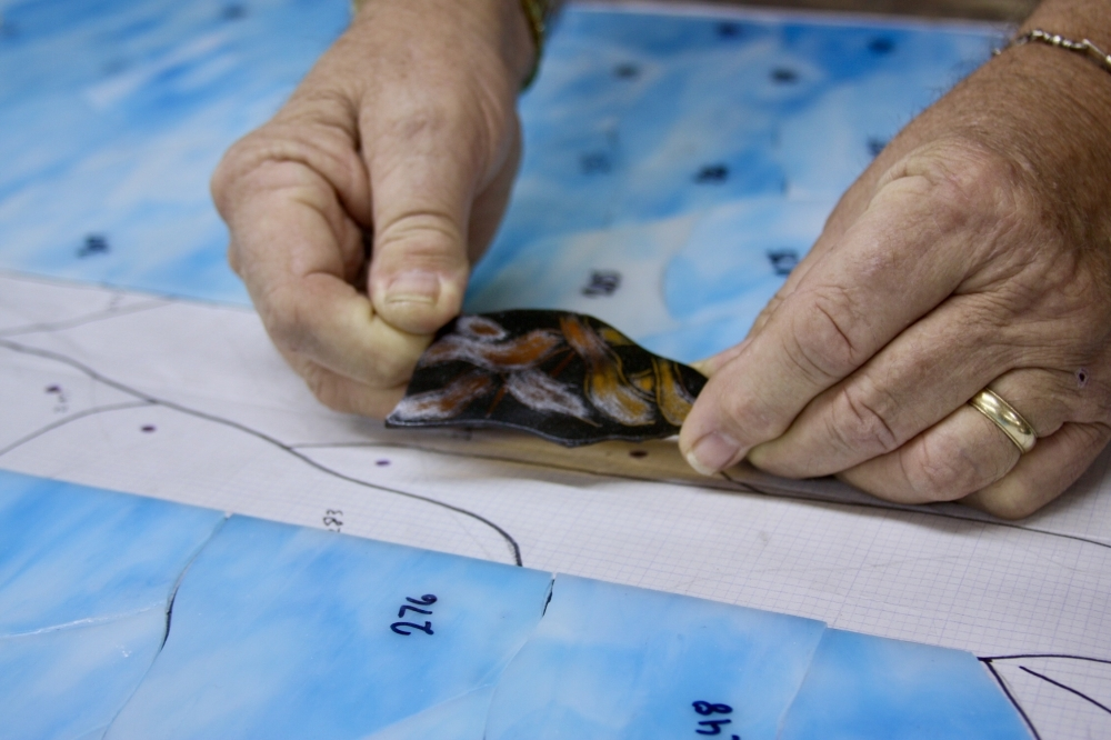 Paint is applied to some pieces of glass to provide more detail in the design. (Lauren Canterberry/Community Impact Newspaper)