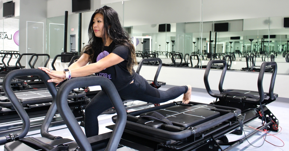 To-ong performs a lunge with resistance on the lagree machine. To-ong said she teaches clients how to do slow, controlled exercises so they leave the session feeling sore and accomplished. (Ally Bolender/Community Impact Newspaper)
