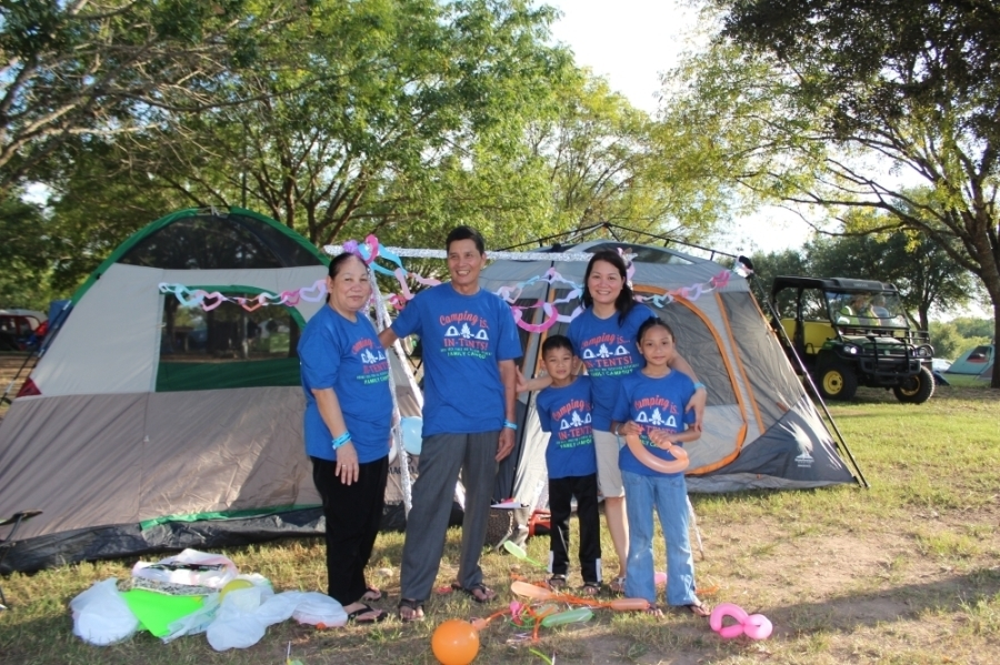 family of five in matching blue t-shirts standing outside by grey tents